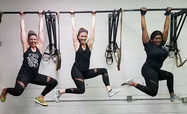 Three women doing pull ups.